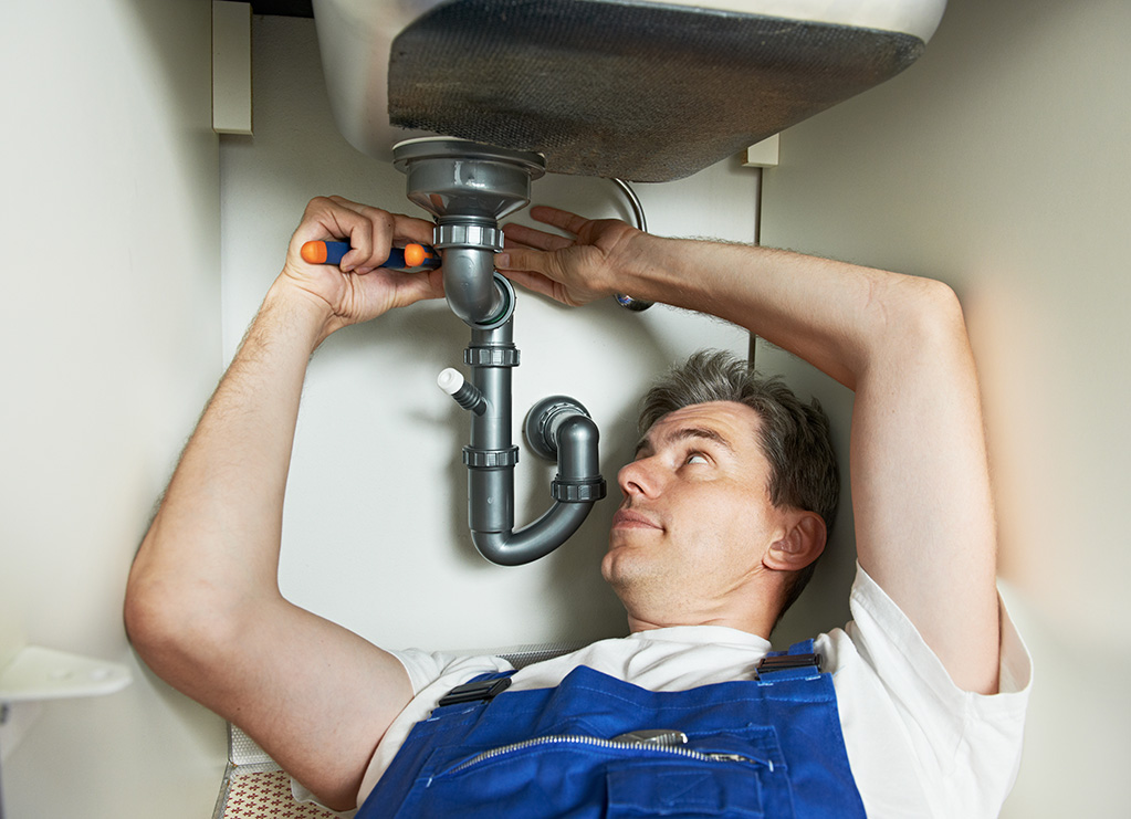 Plumber installing a kitchen sink